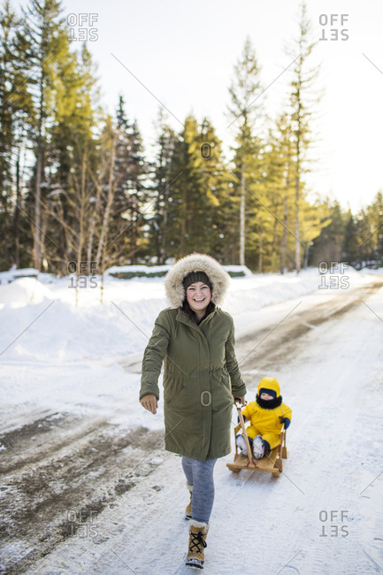 A young active mother pulls son around neighborhood in wooden sled.
