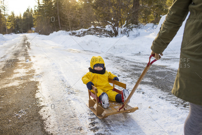 side view of mother pulling her toddler on a wooden sled.
