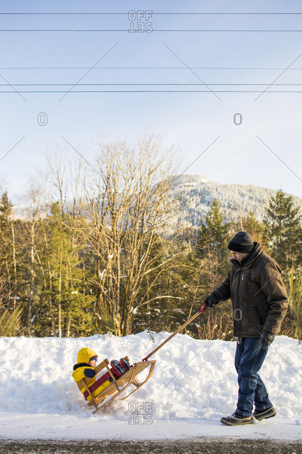 Retired active grandfather pulling his grandson on a wooden sled