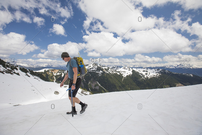 Backpacker hikes across snowfield below Cypress Peak, B.C.