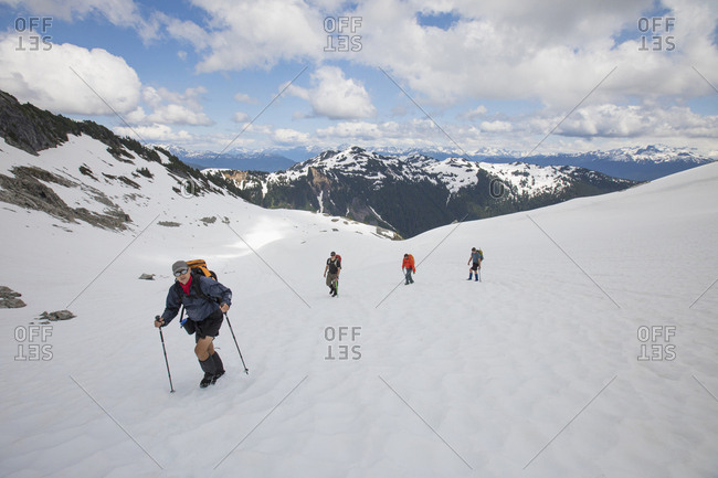 Four mountaineers travel across a glacier towards Cypress Peak.
