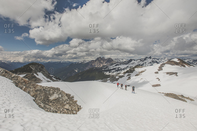 Four mountaineers traverse across a glacier towards Cypress Peak.