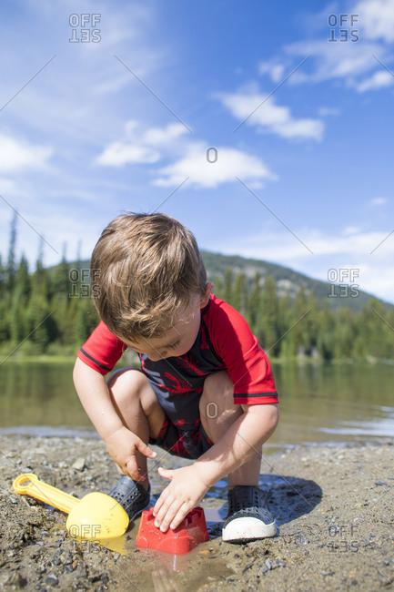 Toddler boy playing at Lightning Lake in Manning Provincial Park.