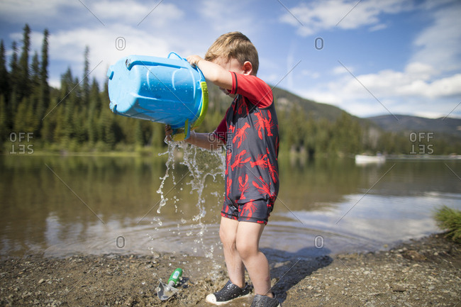 Toddler boy playing with a bucket and shovel at the lake.