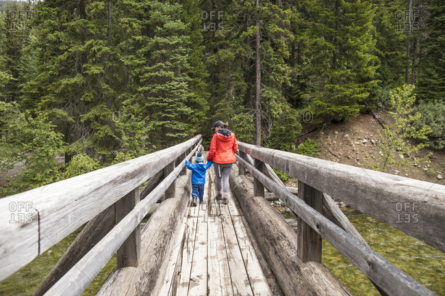 Mother and son hike across a wooden bridge in Manning Provincial Park.