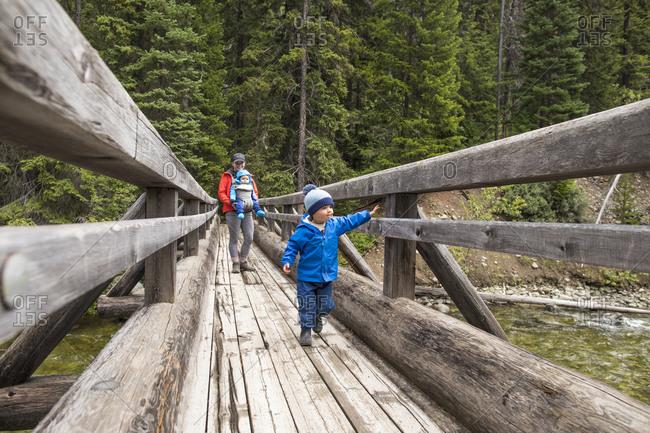 Adventurous mother walks across bridge with her two children
