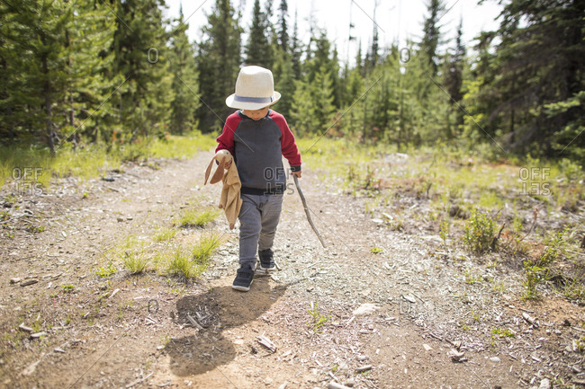 Young care-free boy walking on dirt path with walking stick and bunny
