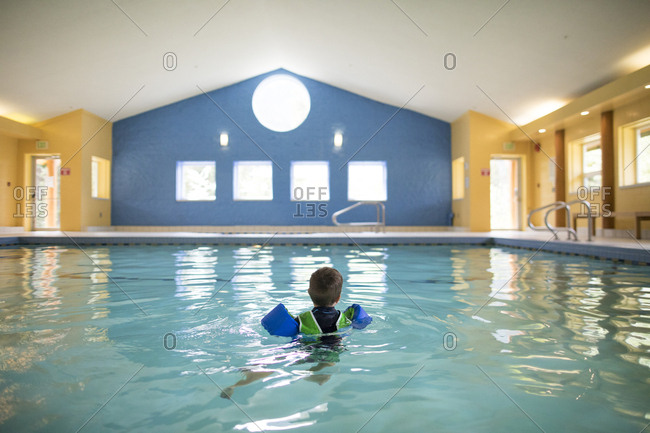 Toddler boy swims alone in indoor pool.