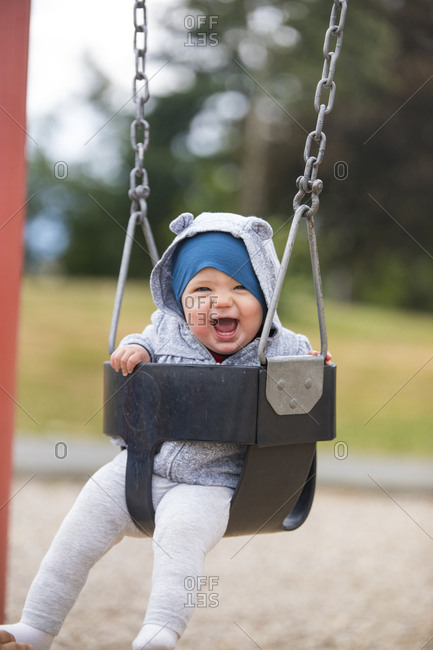 Happy baby on the swing at park.
