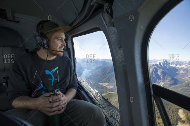 Man looking down at view from widow seat in helicopter, B.C. Canada.