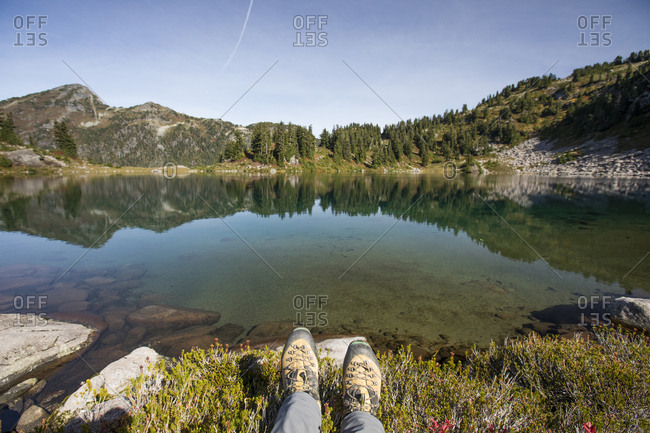 Mountaineering boots in front of picturesque alpine tarn, B.C.