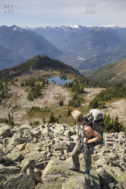 Backpacker looks down toward a tarn and alpine meadow in B.C., Canada.