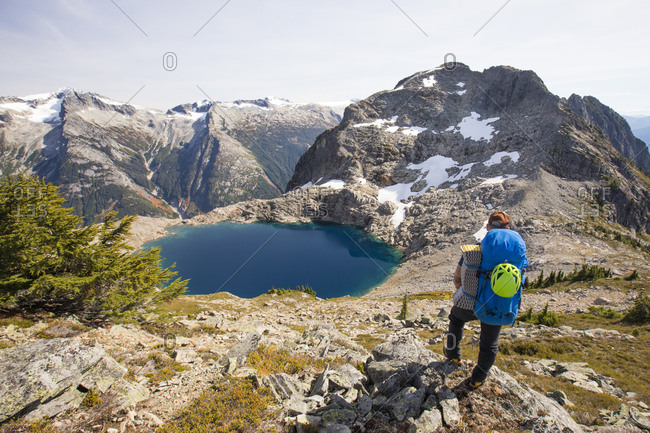 Backpacker looks at view of tarn and Douglas Peak, British Columbia.