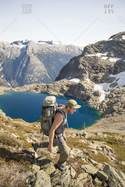 Backpacker hiking above alpine tarn, British Columbia, Canada.