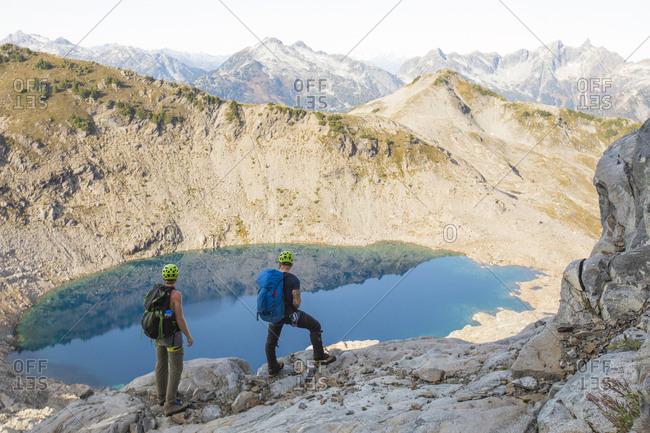 Mountaineers look down on alpine tarn and surrounding peaks.