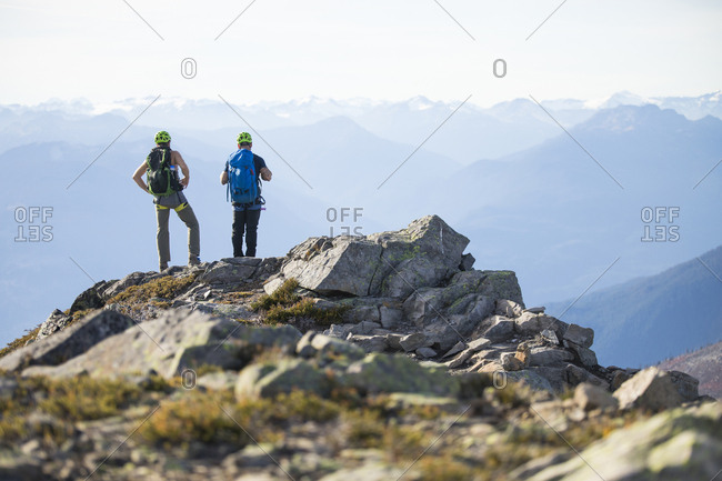 Two climbers stand on the summit of Douglas Peak, British Columbia.
