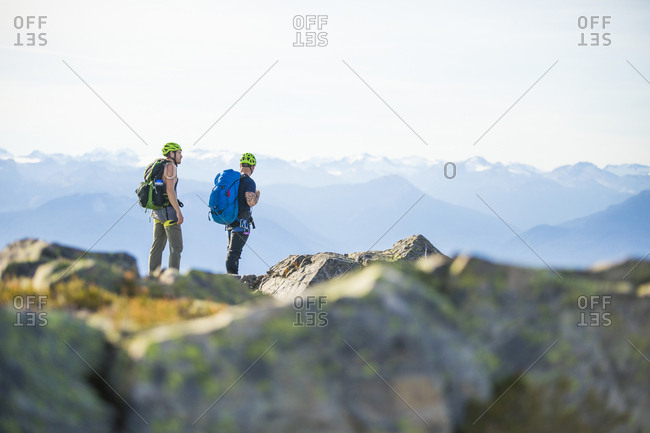 Two backpackers stand on summit of rocky mountain, B.C., Canada.