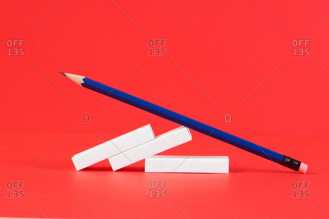 Back to school still life with pencil, ruler, erasers and sharpener on red background
