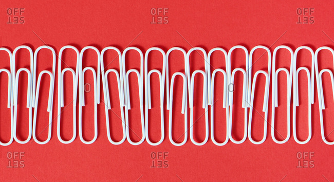 White paperclips on red background.