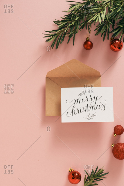 Flowers, envelope and red ornaments on pink background. Christmas gifts, concept.