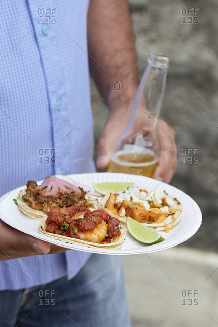Man with food from a taco food truck holding a bottle of beer