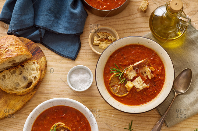 Warm tomato vegetable soup on a wooden table served with ciabatta croutons. Comfort food