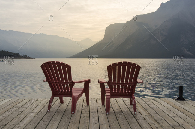 Chairs on jetty over Lake Minnewanka against mountains at Banff National Park