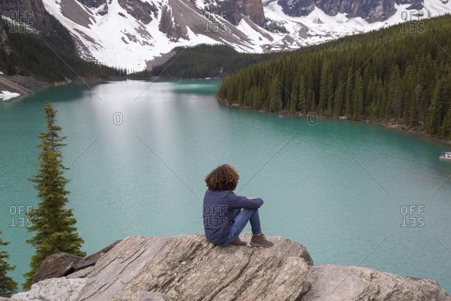High angle view of hiker sitting on rock against Moraine Lake