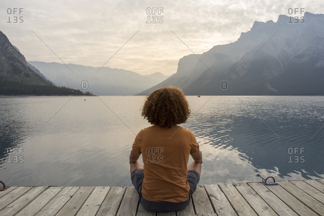 Hiker looking at view while sitting on jetty over Lake Minnewanka against mountains