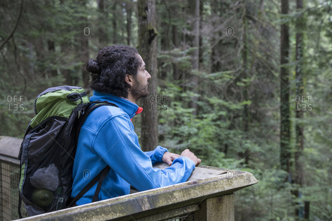 Hiker with backpack looking away while standing at observation point in forest