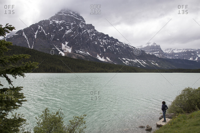 High angle view of hiker standing on rock by Waterfowl Lake against mountains