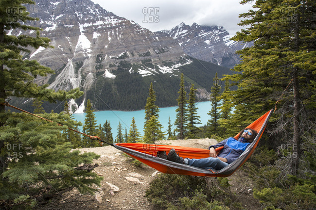 High angle view of hiker resting in hammock against Peyto Lake and mountains at Banff National Park