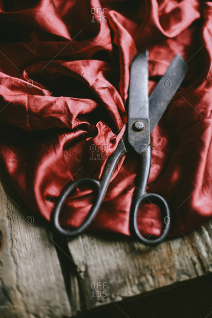 High angle view of scissors with red fabric on wooden table