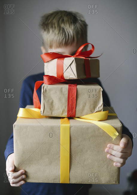Boy carrying wrapped gifts at home