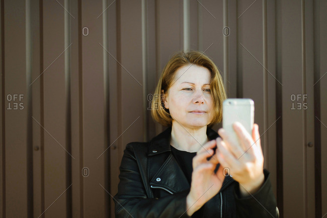 Woman taking a selfie on the street.