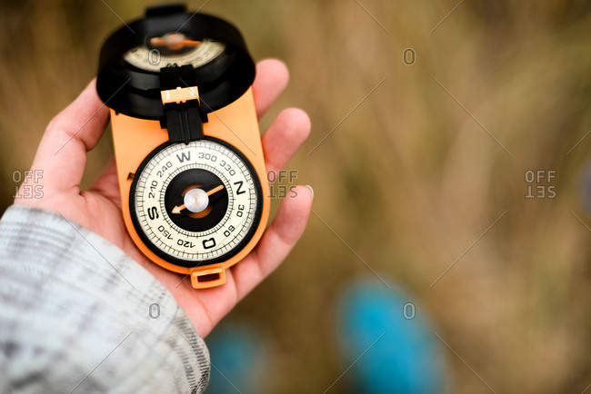 Hand of a woman in the outdoors using a compass to navigate