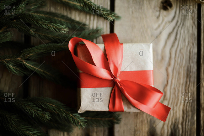 Christmas presents in red ribbon on a wooden background