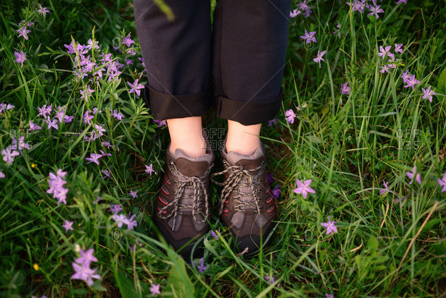 Low section of woman wearing Hiking boots while standing on pink flowed