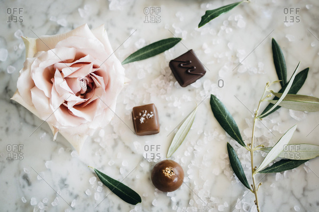 Overhead view of chocolates and rose with leaves amidst sugar on table