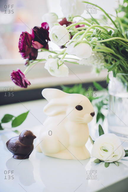 Close-up of Easter bunny and chocolate bird by vase on table