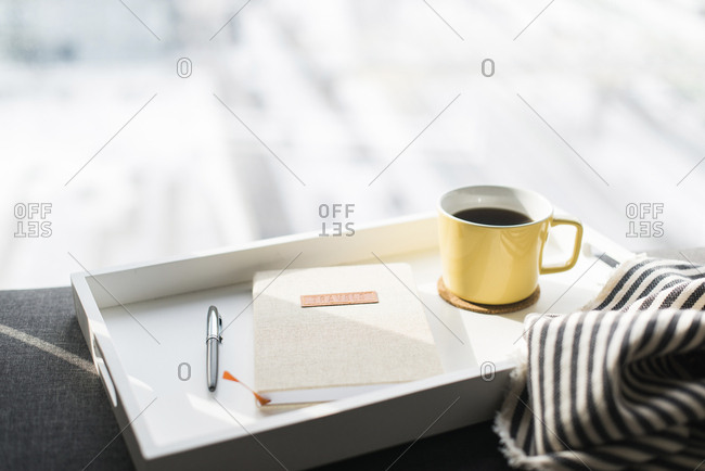 Close-up of diary between pen and coffee cup in tray on sofa