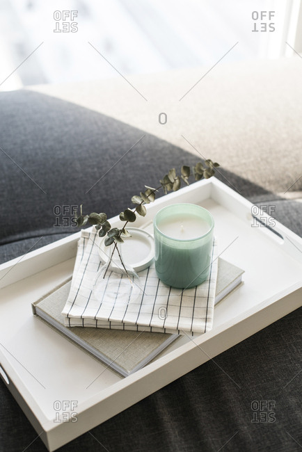 Close-up of twigs in vase on diary by candle