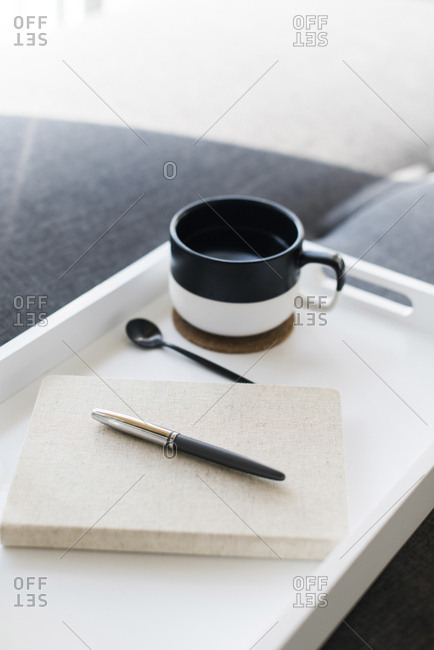 Close-up of pen on diary by coffee cup in tray
