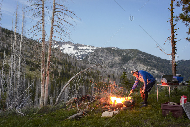 Side view of hiker burning wood in campfire at campsite against mountains