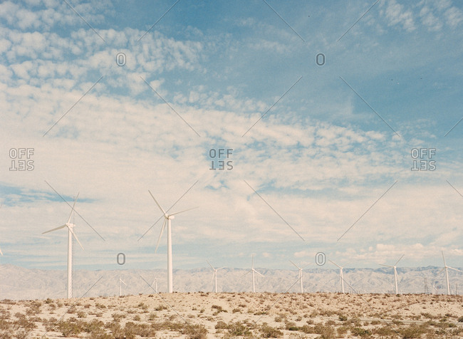 desert landscape with windmills and cloudy sky