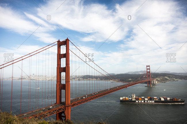 San Francisco, CA, USA - July 13, 2014: A cargo ship passes under the Golden Gate bridge in San Francisco, CA