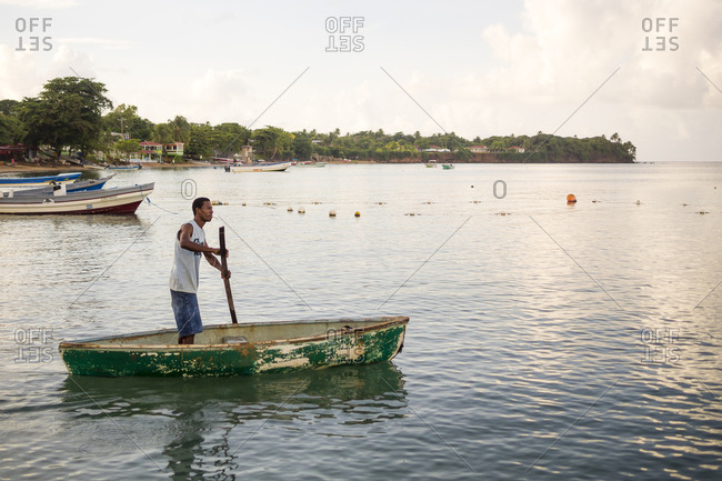 Little Corn Island, Little Corn Island, Nicaragua - August 24, 2012: A local fisherman poles his boat on Little Corn Island, Nicaragua.