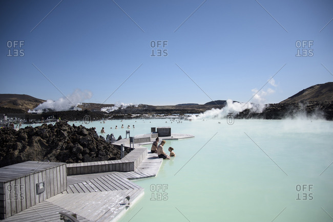 Iceland, Blue Lagoon - February 26, 2017: Friends in Blue Lagoon against clear blue sky