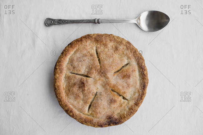 Overhead view of apple pie by spoon on table