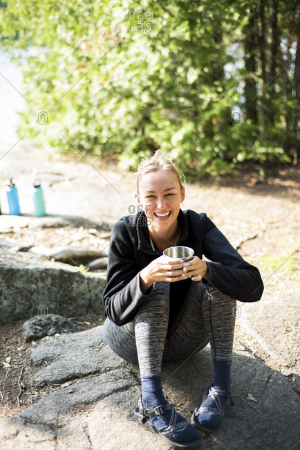 High angle view of cheerful woman having coffee while sitting at campsite